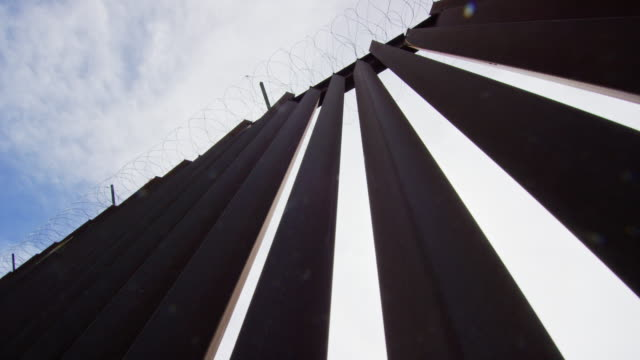 looking up shot of the steel-slat border wall (on the us side) between mexico and the united states with razor wire at the top on a partly cloudy day - international border barrier stock videos & royalty-free footage
