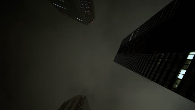 looking up skyscrapers in shinjuku - 暗い点の映像素材/bロール