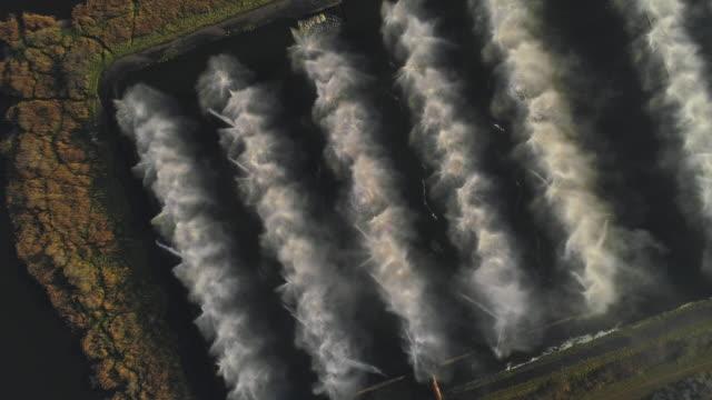 vidéos et rushes de regardant vers le bas directement au-dessus de la vue aérienne de drone des fontaines industrielles sur des bassins de refroidissement de la centrale thermique. - rafraîchissement