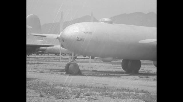 Looks like B29 covered in protective plastic pan to other planes on airfield / plane covered mountains through haze in bg / plane propellers turning...