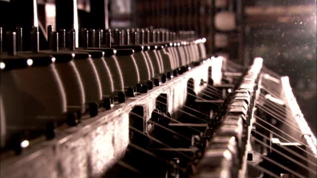 A loom pulls cotton threads from spools in a textile mill. Available in HD.