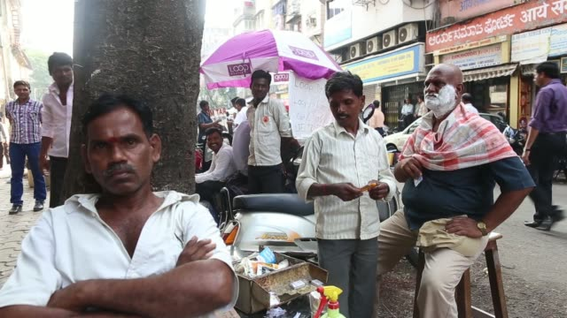 A Loop mobile sim card vendor sits with others by a motorbike in the Fort area of Mumbai India on Wednesday Dec 4 A man stands in the street with a...