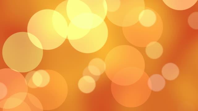vídeos y material grabado en eventos de stock de partículas en bucle flotante en en cámara lenta. - fondo naranja