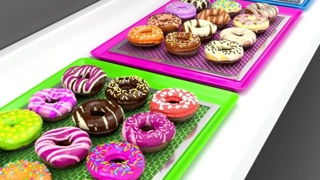 vídeos y material grabado en eventos de stock de loopable bandejas de buñuelos colorido en transportadora (3d render) - brightly lit