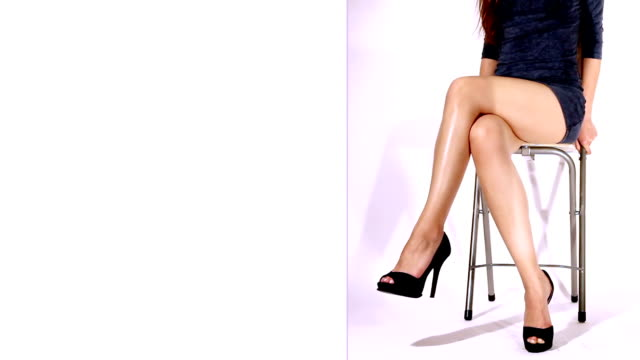 loopable video of sexy legs of a young kittenish woman - cross legged stock videos & royalty-free footage