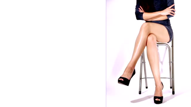 loopable video of sexy legs of a young serious woman - cross legged stock videos & royalty-free footage