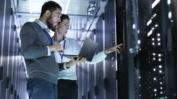 Looped Cinemagraph: Male and Female IT Engineers Standing in the Working Data Center with Server Racks LED Lights Blinking.