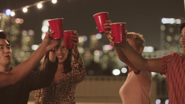 looping vintage video of group of friends dancing and cheering glasses on rooftop party at night - roof stock videos & royalty-free footage