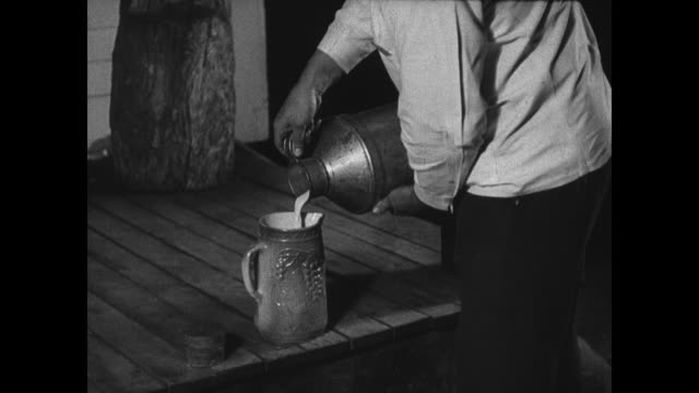 'Loose' milk being poured into pitcher w/ scoop male paying grocery man Milk being poured from pitcher on porch from milk jug to pitcher milk bottles...