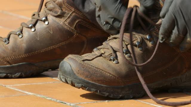 loosen shoe laces - ブーツ点の映像素材/bロール