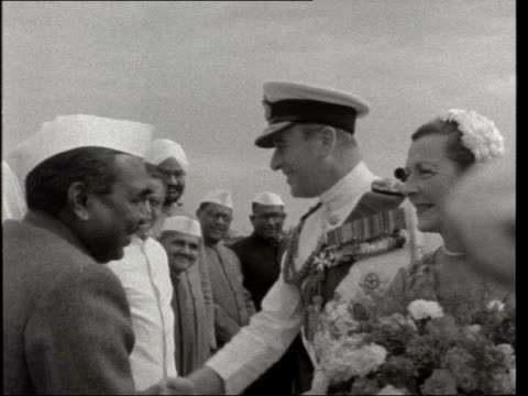 stockvideo's en b-roll-footage met lord and lady mountbatten in india; india: delhi: ext gv england flag gvs vips waiting gvs lord mountbatten and lady mountbatten from plane - greeted... - mahatma gandhi