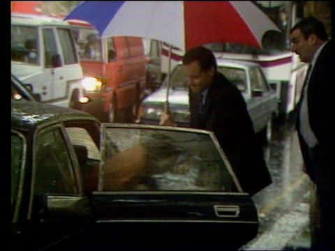 lord archer holding umbrella out to cover wife mary as she gets out of car - クリシュナン・グルマーフィ点の映像素材/bロール