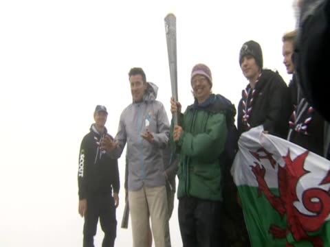 Lord Coe stands with Boy Scouts from Gwynedd in Wales as they hold the Paralympic Torch at the summit of Snowdon