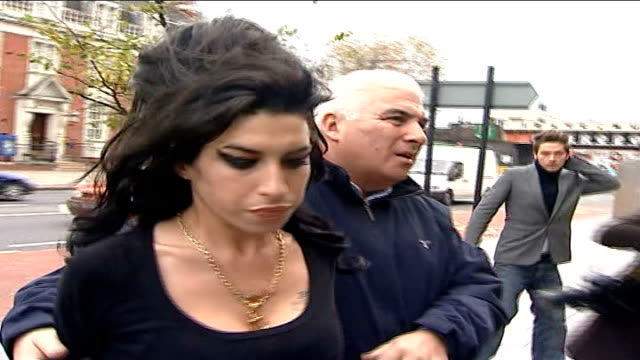 lord lloyd webber defends amy winehouse after fans boo her; london: thames magistrates court: ext winehouse along with minders to court - amy winehouse stock-videos und b-roll-filmmaterial