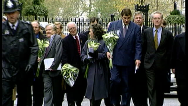 lord morris dies aged 84; t23119914 / tx downing street: lord morris and campaigners from haemophilia society towards with bouquets of white lilies... - white点の映像素材/bロール