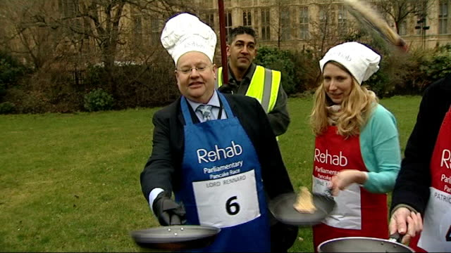 nick clegg response r12021311 / westminster victoria tower gardens lord rennard tossing pancake at parliamentary pancake race lord rennard talking to... - クリス・レナード点の映像素材/bロール