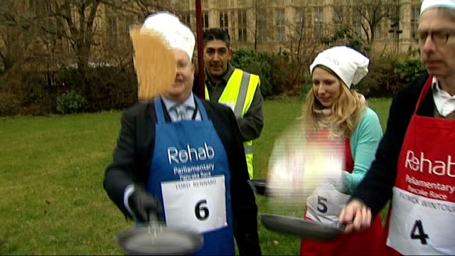 nick clegg response r12021311 / westminster victoria tower gardens lord rennard tossing pancake at parliamentary pancake race - victoria tower stock videos & royalty-free footage