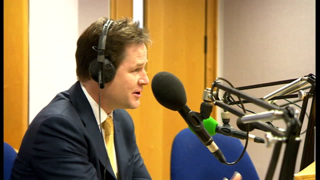 police looking at formal complaints cutaway of nick clegg mp seated in radio studio during bbc radio solent interview - クリス・レナード点の映像素材/bロール