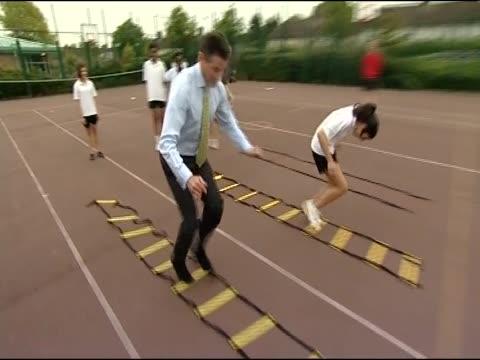 vídeos de stock, filmes e b-roll de lord sebastian coe races children in playground while promoting london 2012 olympic games - sebastian coe