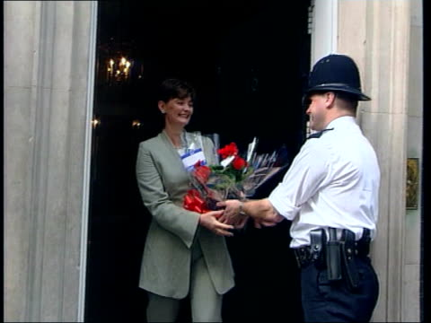 Lord Winston attack on Government policy LIB Downing Street EXT Cherie Blair receiving flowers at door of Number 10 ZOOM IN