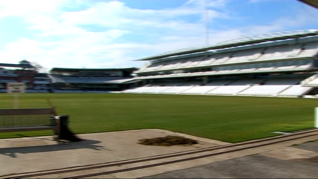 London Lords Cricket ground EXT Lords cricket pitch and empty stands / Lords Cricket pitch wicket and empty stands and pavilion seen at pitch level/...