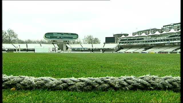 stockvideo's en b-roll-footage met lord's cricket ground: mcc museum; england: london: lord's: ext cricket players walking onto the pitch / long shot of players / solitary spectator... - cricketveld