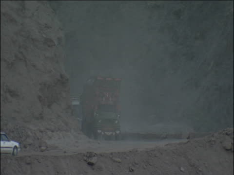 Lorries and cars pass on dusty road