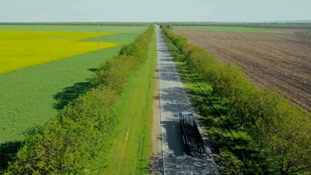 lorry with metal rods driving along road. aerial view. - rod stock videos and b-roll footage