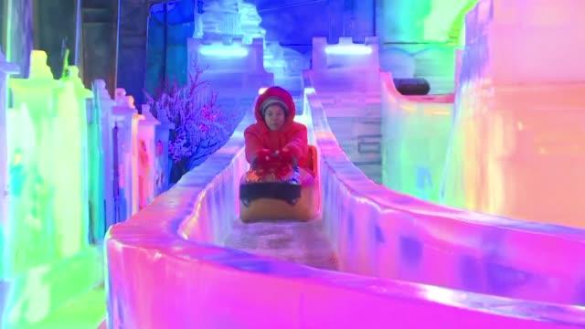 los acalorados habitantes de bangkok acuden en masa a parques de hielo y nieve para cambiar el calor típico de su pais por temperaturas bajo cero - hielo video stock e b–roll