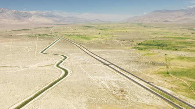 ws aerial pov los angeles aqueduct winding along foothills of sierra nevada with us highway 395 cutting across owens valley desert, inyo mountain in background / california, united states  - basin and range province stock videos and b-roll footage