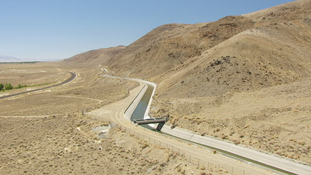 ws aerial pov los angeles aqueduct winding along foothills of sierra nevada with us highway 395 cutting across owens valley desert / california, united states  - aqueduct stock videos and b-roll footage