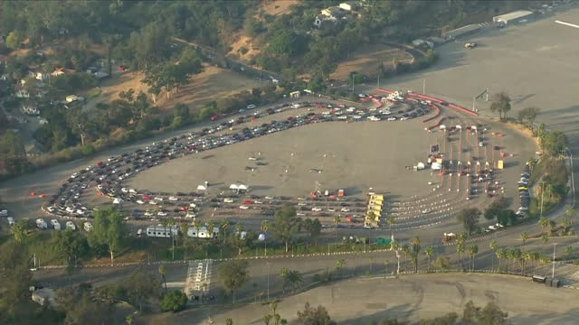 los angeles, ca, u.s. - aerial view of people in cars queuing for covid-19 testing at dodger stadium. on tuesday, november 24, 2020. - dividing line stock videos & royalty-free footage