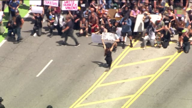 ktla los angeles ca us aerial view of protestors with placard and riot police on santa monica street during george floyd protest on sunday may 31 2020 - soziale gerechtigkeit stock-videos und b-roll-filmmaterial
