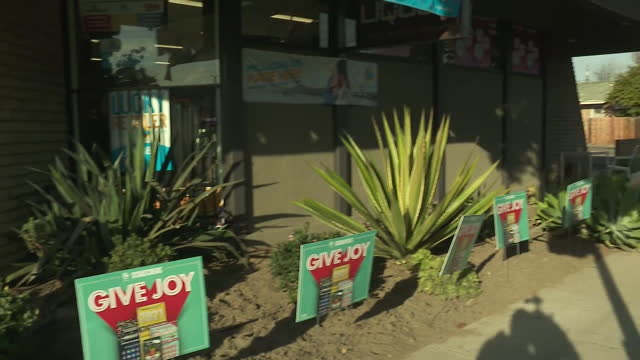 stockvideo's en b-roll-footage met los angeles, ca, u.s. - entrance to lottery store with its signage in los angeles. on wednesday, january 13, 2021. - loterijlootje