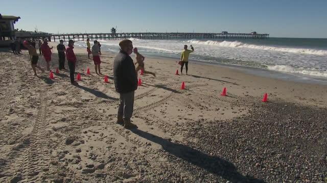 vídeos de stock, filmes e b-roll de los angeles, ca, u.s. - finish line of seasonal ocean lifeguard tryouts in san clemente on monday, february 22, 2021. - touca de natação