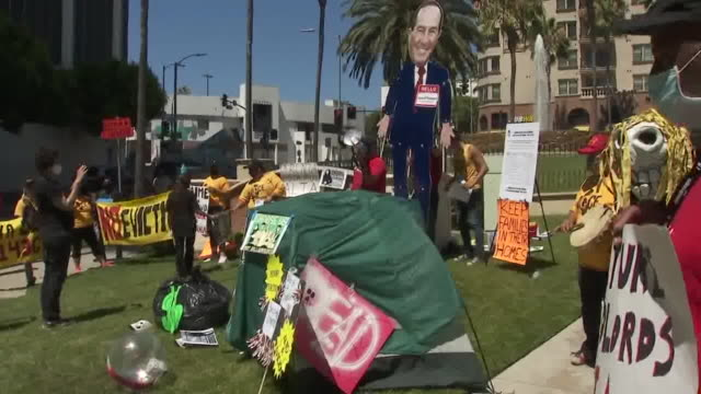los angeles, ca, u.s. - group of protestors with banners and cardboard cutout of los angeles' mayor at a protest demanding the city cancels rents and... - male likeness stock videos & royalty-free footage