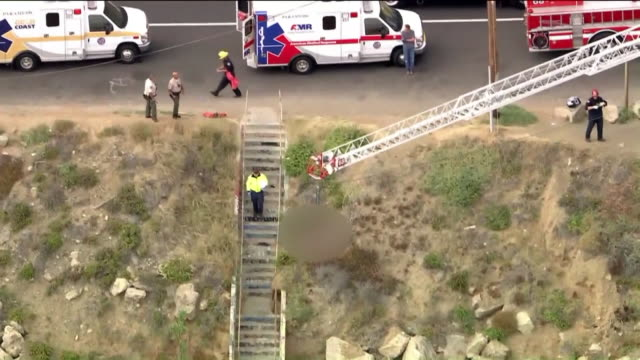 los angeles, ca, u.s. - various shots of rescue operation. three people died thursday afternoon when they were swept off a cliff near point mugu... - sitting stock videos & royalty-free footage