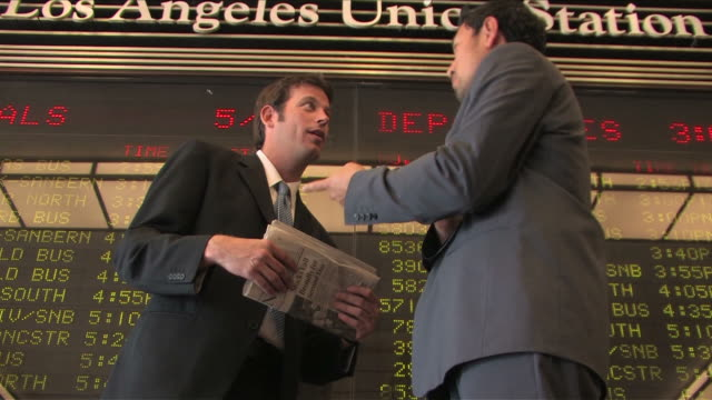 vídeos de stock e filmes b-roll de los angeles, california, usatwo business men are talking on the business at the train station - fato completo