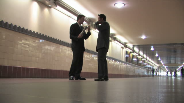 Los Angeles, California, USATwo business men are talking on the business at the train station