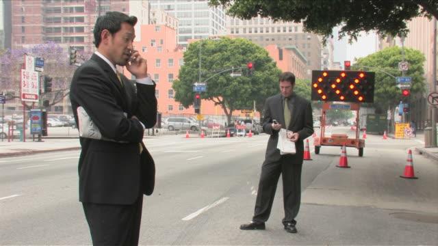 vídeos de stock e filmes b-roll de los angeles, california, usatwo business men are  talking on the mobile phone - fato completo