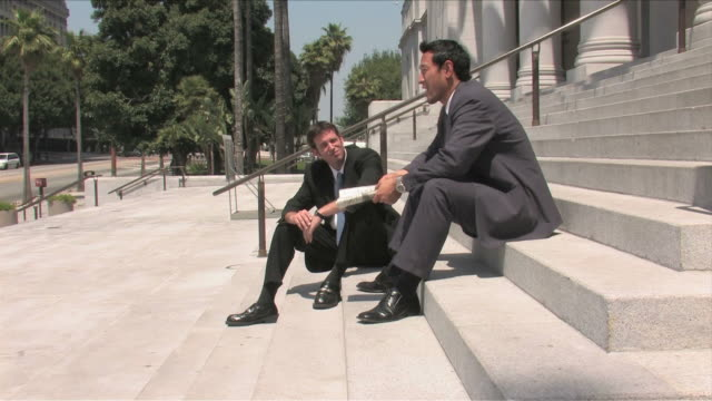 Los Angeles, California, USATwo business men are talking on the business on the street