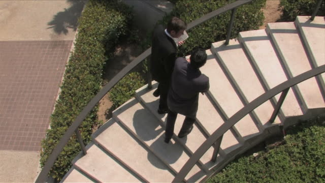 Los Angeles, California, USATwo business men are  walking and talking on the stairs