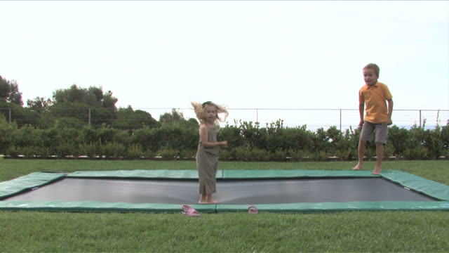 stockvideo's en b-roll-footage met los angeles, california, usatwo kids are playing and jumping at the playground - trampoline
