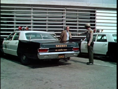 vidéos et rushes de 1970 montage los angeles county courthouse, man being escorted by police from police car, los angeles, california, usa, audio - 1970
