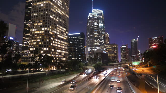 los angeles downtown financial and business district skyline and traffic on 110 freeway at night, 4k - financial district stock videos & royalty-free footage