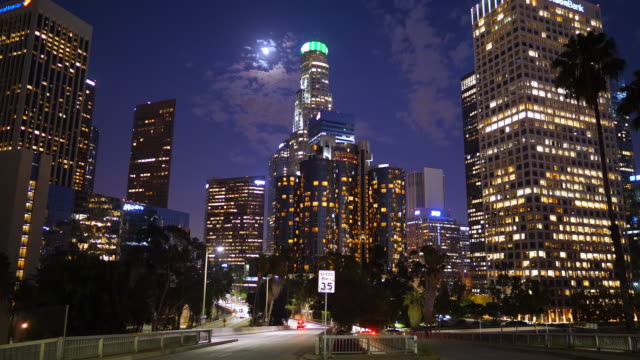 vidéos et rushes de los angeles downtown financial and business district skyline at night and cars driving on the street, california, 4k - montrer la voie