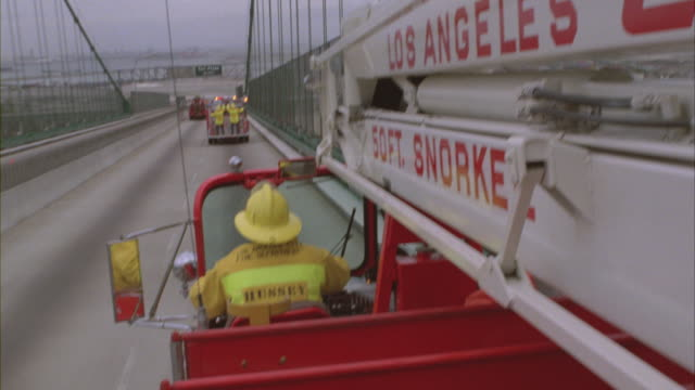Los Angeles fire trucks speed over the Long Beach Bridge onto the California freeway.