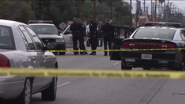 stockvideo's en b-roll-footage met los angeles police department in sylmar at at an active crime scene on april 23, 2015. close-up of yellow tape, pd setting up tape, police cars. - afzetlint