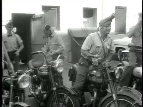 Los Angeles police officers put on gas masks get on their motorcycles and drive away
