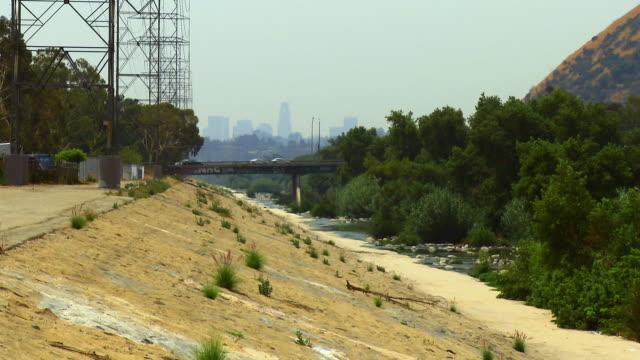 MS, Los Angeles River concrete flood control channel, cityscape in distance, Glendale, California, USA